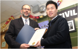 Ben Sherman, (l.) the principal of the East-West School of International Studies, accepts a citation from David Ng from Assemblywoman Nily Rozic's office. Photo by Christina Santucci